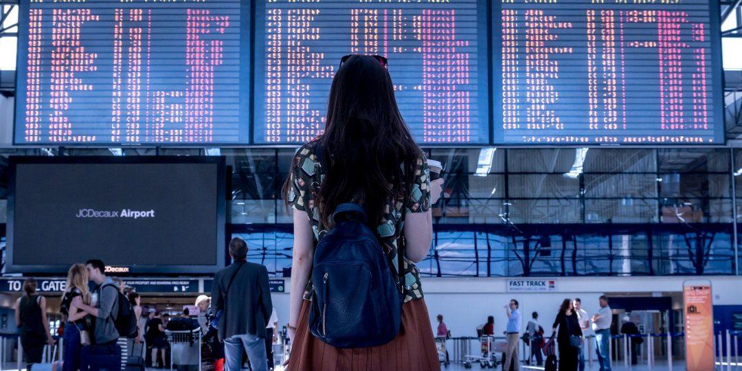 Imagen de portada: mujer joven viendo horarios de avión