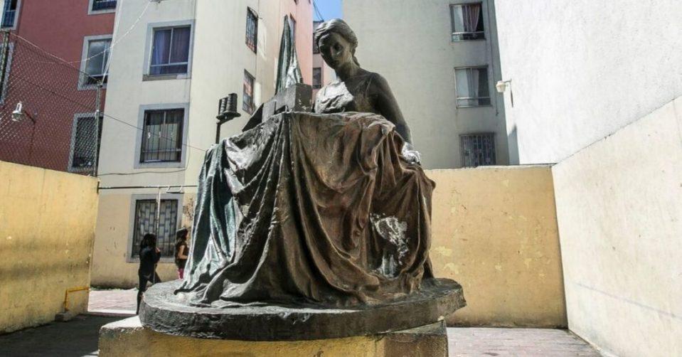 Estatua de bronce de una mujer cosiendo una bandera de Mexico