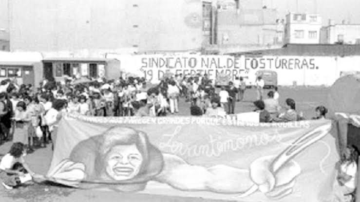 """Mujeres sosteniendo pancarta con la leyenda """"a los grandes nos parecen grandes porque estamos de rodilla ¡levantémonos!, detrás se observa una pared con el nombre"""" Sindicato Nal. De Costureras 19 de Septiembre"""""""