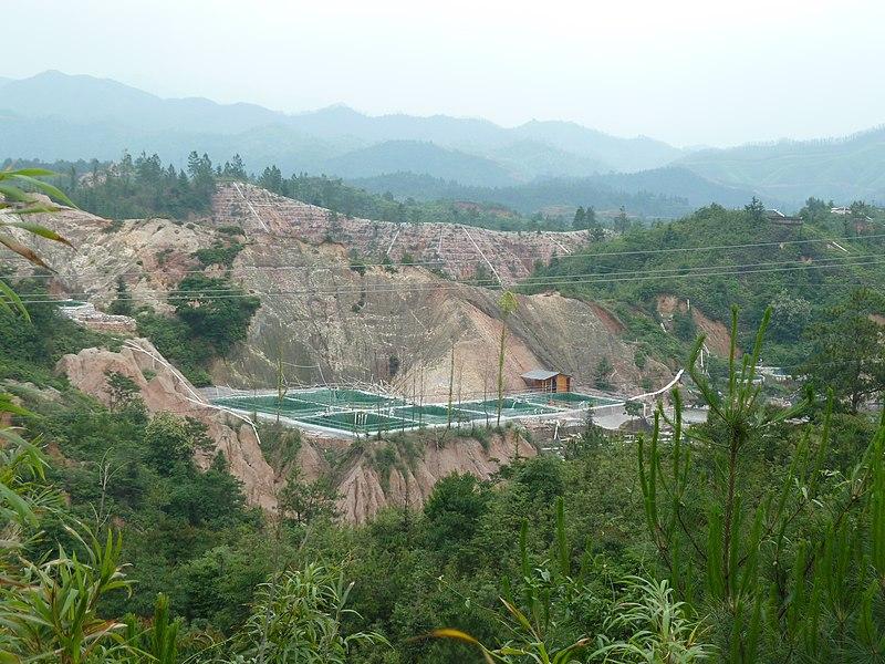 Imagen de una mina a cielo abierto en China, donde se observa una zona deforestada en medio de una zona selvática