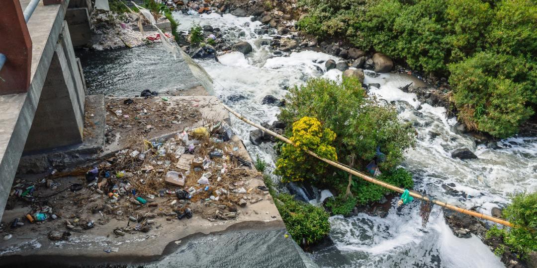 Rio corriendo debajo de un puente con basura en el centro.