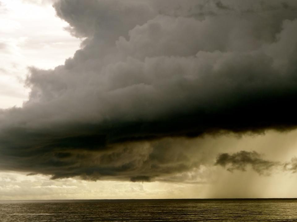 Foto de una nube alta soltando un poco de lluvia sobre el océano