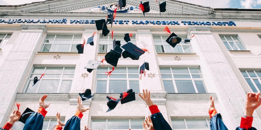 Grupo de estudiantes recien graduados lanzando su birrete al cielo frente a un edificio de la universidad