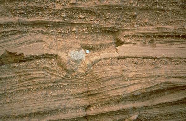 Foto de un depósito volcánico de cenizas. Una bomba (un pedazo de roca de más de 10 cm) está deformando los depósitos de ceniza creando una estructura cóncava.