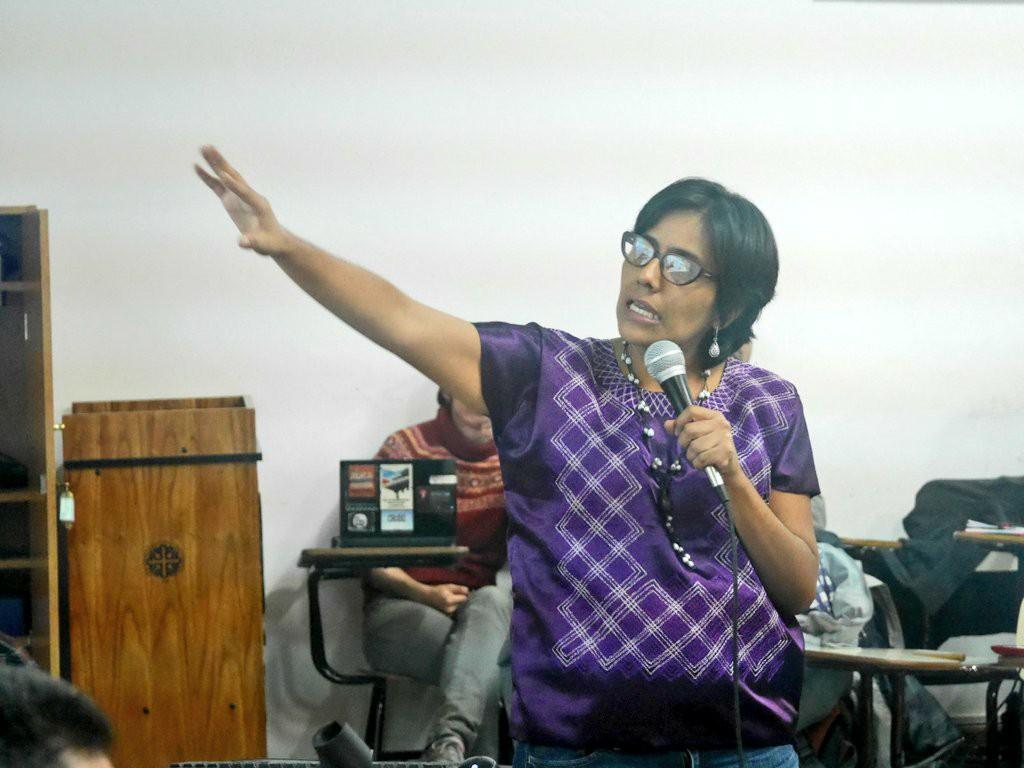 Alejandra Jiménez vistiendo un huipil  morado. Sostiene un micrófono con la mano izquierda y senala con su mano derecha.